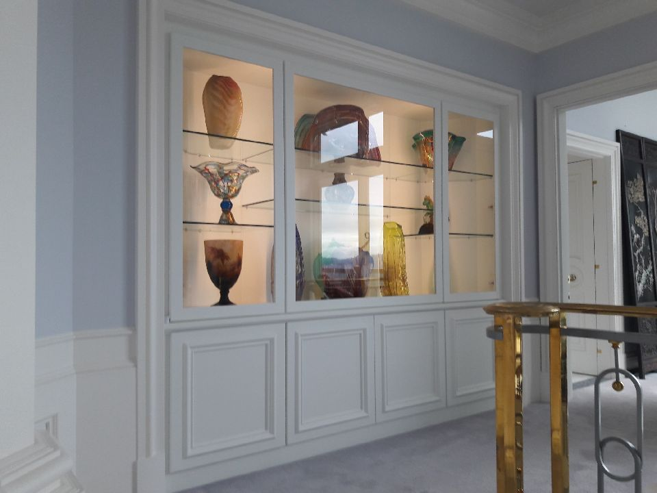 vertical image of pantry decorated with vases behind glass